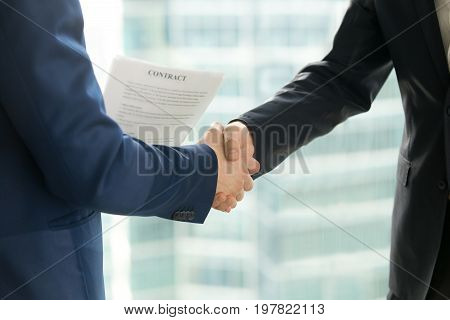 Businessmen handshaking, male hands shaking, holding contract on city building background, employment and hiring, enterprisers making good business deal after successful negotiations, close up view