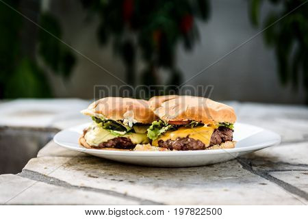 Home Made Burgers On A Plate On Stone Paved Terrace.
