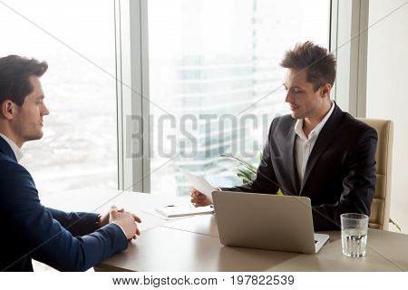 Focused businessman studying document, examining written business offer at meeting with partner, boss checking report sitting at desk, recruiter reviewing resume of applicant during job interview