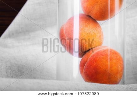 Close-up of whole tasteful red peaches on a white tablecloth background. Three healthful and organic peaches in a transparent glass. Ingredients for nutritious summer breakfast. Copy space.