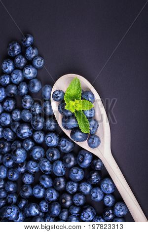 A fantastic composition of fresh, ripe and juicy blueberries with green mint in a light wooden spoon on a dark purple background. Summer berries full of nutritious vitamins. Healthy food.