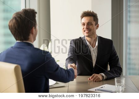 Two cheerful businessmen shaking hands over office table, starting negotiations, hr greeting applicant arrived at job interview with handshake, good first impression, forming beneficial partnership