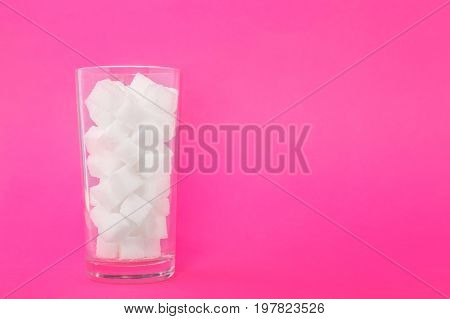 A glass of sugar crystals or cubes on a bright pink background. Sweet food ingredient for cooking, baking, and beverages. Intake of bad calories.