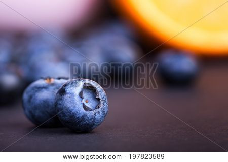 A close-up of two nutritious blueberries on a purple blurred background. Tasteful and ripe bilberries. Refreshing and healthful blueberries for sweet, summer smoothies and desserts. Copy space.