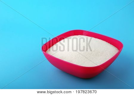 A bright pink box full of sweet rumbly sugar on a blue background. Consumption of bad calories. White organic sugar and sweet food ingredient. The sugar for cooking, baking and drinks.