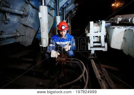 young coal miner is underground in mine for coal mining in overalls against backdrop of mining equipment. concept of repair of industrial equipment. concept hard work, metro, extraction of gold, metal, minerals.