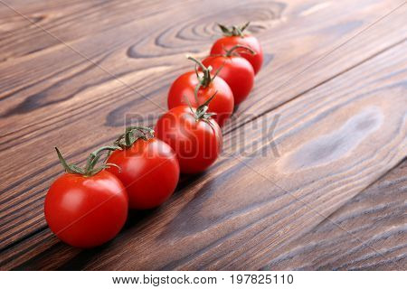 A line of fresh, ripe and bright red tomatoes on a light brown wooden background. A close-up of rustic tomatoes. Delicious cherry tomatoes. Healthful autumn vegetables. Vegetarian food.
