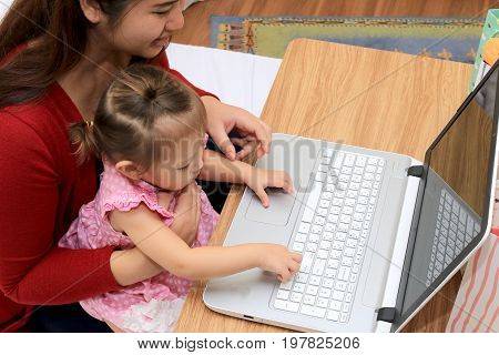 Pregnant Mother Shopping Online And Working For Her Baby With Laptop Computer Working In Bedroom Fro