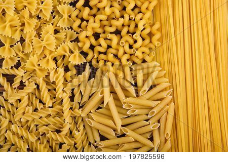 Beautiful assortment of pasta on a wooden background. Different kinds of perfectly organized macaroni. Delicious farfalle, fettuccine, noodles, fusilli and penne rigate. Traditional italian cuisine.