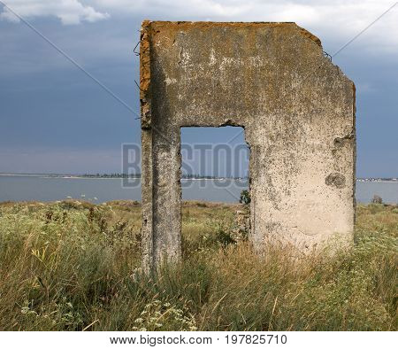 Old concrete doorway of the time of World war two. Island Berezan in Ukraine Black Sea. Seascape view