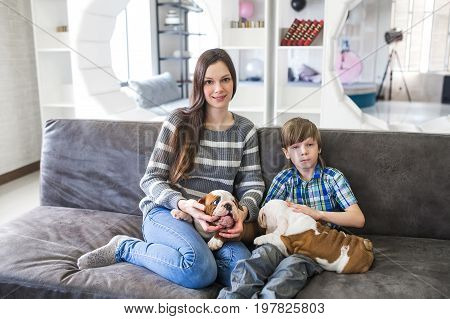 Beautiful mother and son keep the English bulldog puppy.