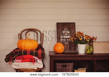 fall at country house. Seasonal rustic decorations with cozy blankets and flowers on wooden background on chair