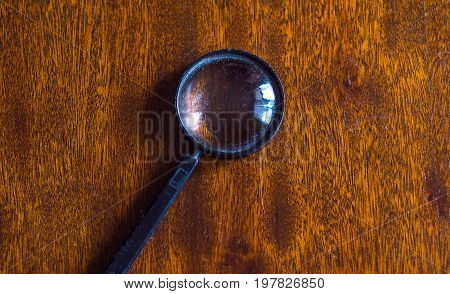dirty magnifying glass or loupe on wooden table