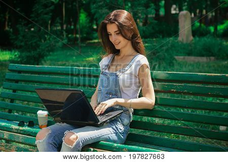 Cutie brunette girl working with laptop outdoors in the park