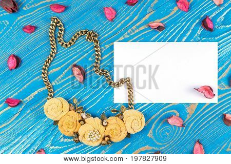 Handmade necklace consisting of five flowers and a greeting card with congratulations on a blue wooden background