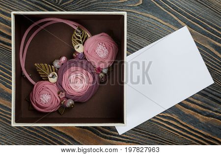 Pink-colored handmade necklace putted in a box and a letter of congratulations are lying on wooden background