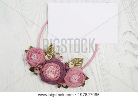 Handmade necklace with pink colored flowers lying on a white wooden background and letter with congratulation