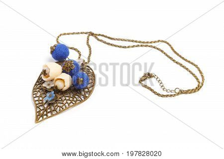 Pendant handmade in the form of original blue balls and flowers on a metal leaf
