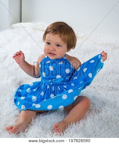 Little girl in a blue dress is sitting on the bed and is holding the edge of her dress