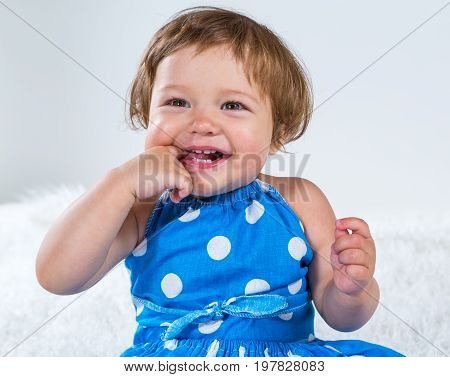 Little girl in a blue dress is sitting and laughing holding her finger in her mouth