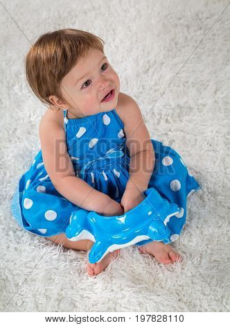 Little girl in a blue dress sits on the bed and looks up