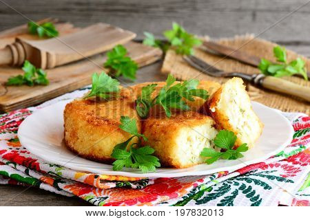 Mixed vegetable cutlets with egg filling on a white plate. Fried cauliflower potato cutlets with egg filling. Homemade vegetarian zrazy recipe. Rustic style. Closeup