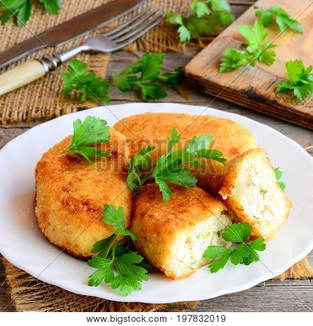 Vegetable cutlets with egg filling on a white plate. Cutlets (zrazy) cooked from cauliflower and potatoes and filled with boiled sliced eggs. Rustic style. Closeup