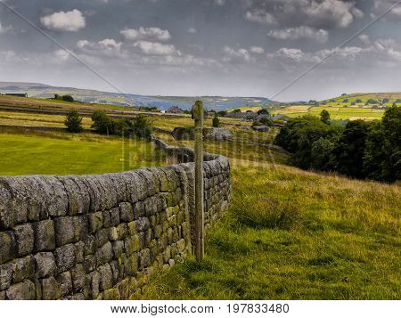 Fields with traditional dry stone wall and wooden sign in yorkshire pennine countryside with trees farms and mountains visible