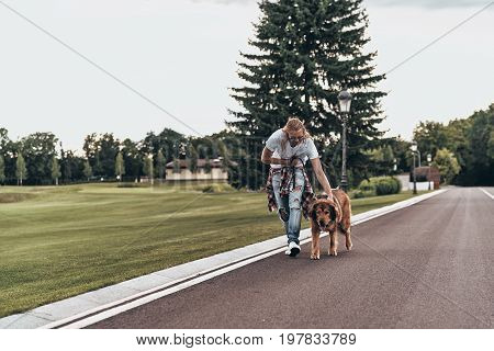 Time for a walk. Full length of handsome young man walking with his dog while spending time outdoors