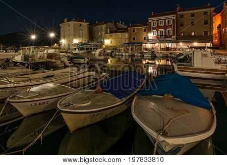 Boats and houses reflected in the water of the old harbour in Cres