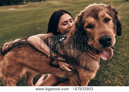 Best friend ever! Beautiful young woman keeping eyes closed while playing with her dog outdoors
