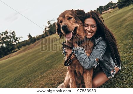 So cute and lovable. Beautiful young woman keeping eyes closed and smiling while embracing her dog outdoors
