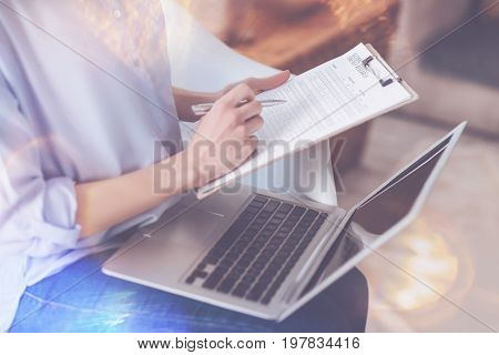 Modern type of work. Pleasant woman using laptop and making notes while working as a freelancer at home