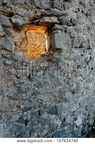 Abstract of the sun shining through a hole in a stone wall near the city of Cres (Croatia)