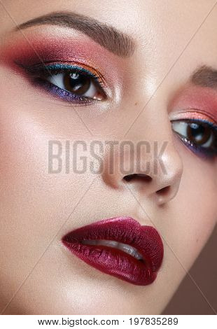Close up portrait of beautiful young model with professional colorful makeup, perfect skin. Trendy colorful smoky eyes. Red lips