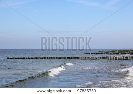 The waters of the Baltic Sea and many breakwaters form the seaside landscape in Kolobrzeg in Poland