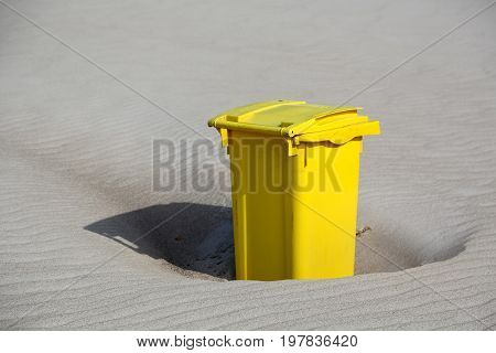 One yellow rubbish bin is located on the sand of the Baltic Sea beach in Kolobrzeg in Poland