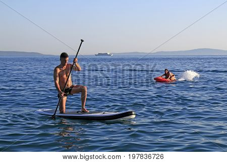 Split Croatia - 12 July 2017: Boy and girl enjoying watersports with electric jet surfing board kymera bodyboard and SUP paddle board on the Znjan Beach