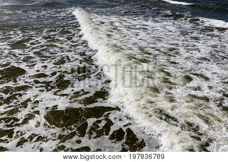 Dark Baltic Sea waters and one wave on its surface. This can be seen close to seashore during windy day in Kolobrzeg in Poland