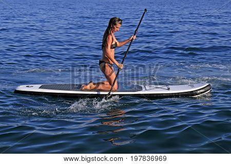 Znjan Beach Split Croatia - 12 July 2017: Girl enjoying watersports paddling on SUP paddle board