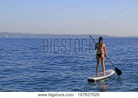 Znjan Beach Split Croatia - 12 July 2017: Girl enjoying watersports standing and paddling on SUP paddle board