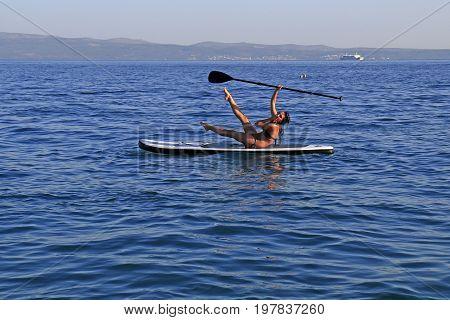Znjan Beach Split Croatia - 12 July 2017: Girl enjoying watersports sitting on SUP paddle board