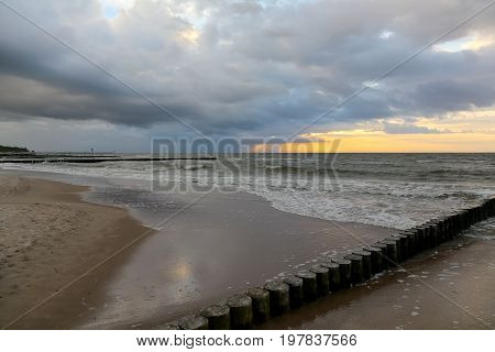 Baltic Sea waves gently affects the sandy beach in Kolobrzeg in Poland. The coast along with wooden breakwaters is illuminated by the gentle glow of the setting sun