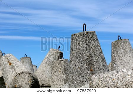 Stacked huge concrete blocks with special shape are shown against the blue sky. These elements of the breakwater protect the coast from the sinister action of the sea waves in Kolobrzeg in Poland