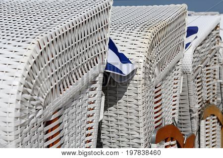 Three roofed beach chairs are shown close up. Side view of these beach furniture can be seen on the beach in Kolobrzeg in Poland