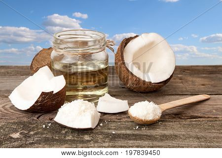 Halfs Of Coconut, Jar Of Coconut Oil, Coconut Flakes On  Blue Cloudy Sky Background.