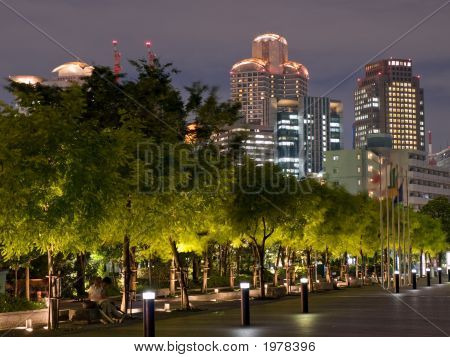 Osaka skyline in the background with trees in the foreground in the evening poster