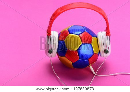 Music And Sports Equipment Concept. Modern Earphones And Football