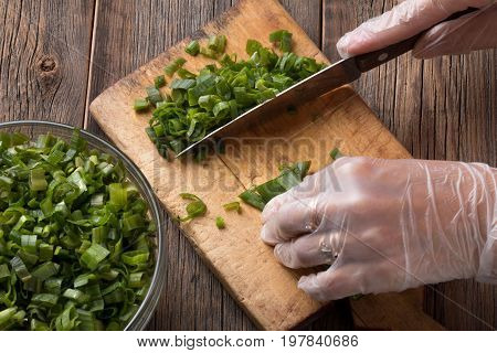 Girl cuts green onions into slices. Sliced green onions.