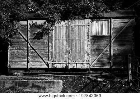 Old railway freight carriage used as a shed black and white image
